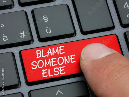 Foto Closeup finger typing on blame someone else key on computer keyboard