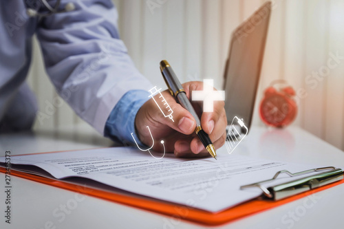 Foto  Doctor in gown uniform using a pen write on medical chart
