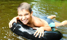 The Boy Has Fun On An Inflatable Tubing In The River.