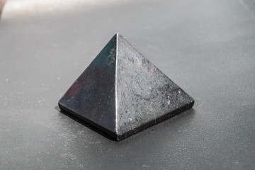 Shungite stone in the shape of a pyramid close up
