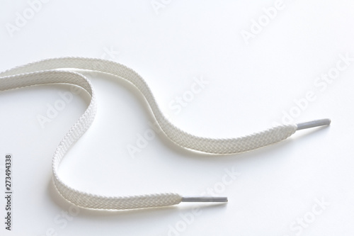 Fotomural  unbound white shoe laces on white background