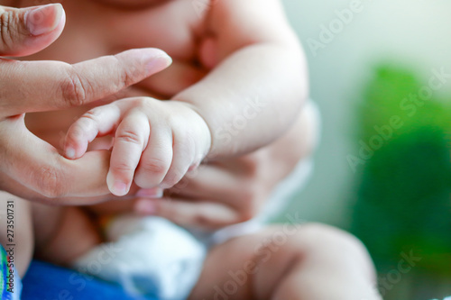Photo  An Asian baby boy does not wear clothes to catch his mother's fingers