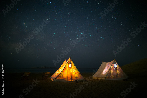 Montage in der Fensternische Camping Camping under stars, night sky in the desert, the Milky Way, tents glowing from the inside. Vacation holidays in nature. Sleep under sky