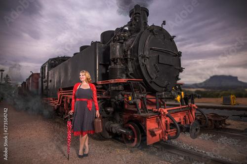 Vászonkép Frau in Petticoat Kleid steht neben einen Dampflok
