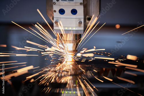 Obraz Laser cutting. Metal machining with sparks on CNC laser engraving maching - fototapety do salonu
