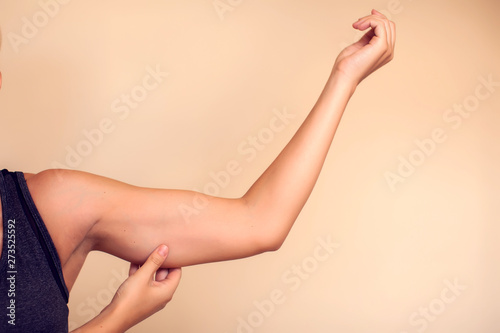 Valokuva Woman touches her tricep. People, healthcare and beauty concept