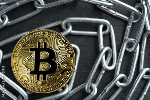 Fotografie, Obraz  Physical Bitcoin gold coin on a convoluted shiny metal chain on dark stone slate plate background