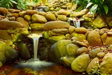 Three Waterfalls In A Small Pond In A Garden