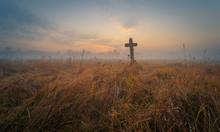 Lonely Ancient Tombstone In Form Of Cross Among High Yellow Grass At The Autumn Foggy Field At Dawn.