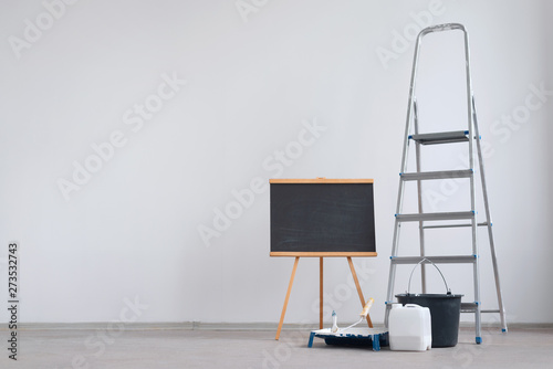 Fotografía  Ladder, blackboard with copy space for to do list and bucket with paint roller on a white wall background