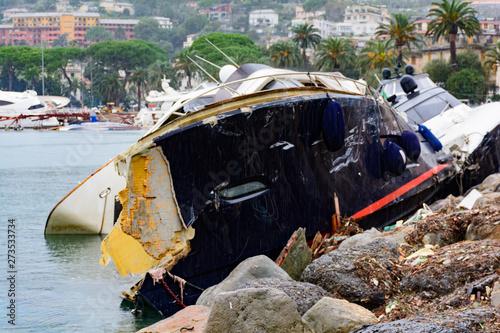 Barca distrutta da una forte mareggiata e incastrata sugli scogli Fototapet