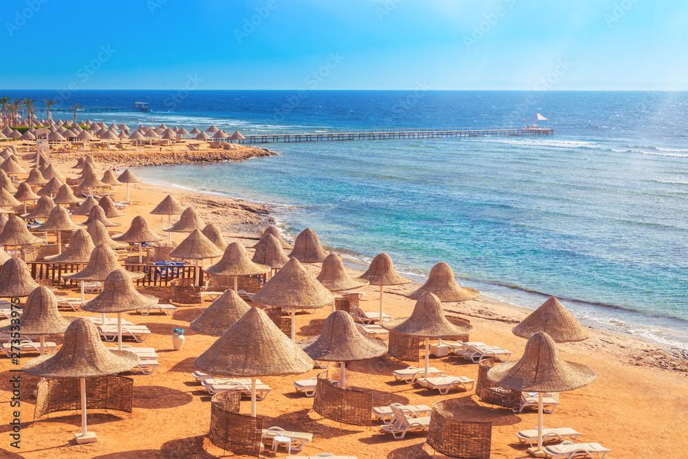 Fototapeta Sandy beach coast line with straw parasols umbrellas and blue sea. Travel destination for vacation concept. Sharm el Sheikh Egypt morning light with copy space