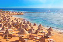 Sandy Beach Coast Line With Straw Parasols Umbrellas And Blue Sea. Travel Destination For Vacation Concept. Sharm El Sheikh Egypt Morning Light With Copy Space