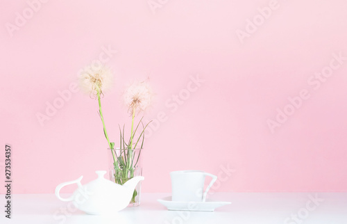 Foto auf Leinwand Lowenzahn White porcelain teapot and cup on pink background with white dandelions. Concept for festive background.