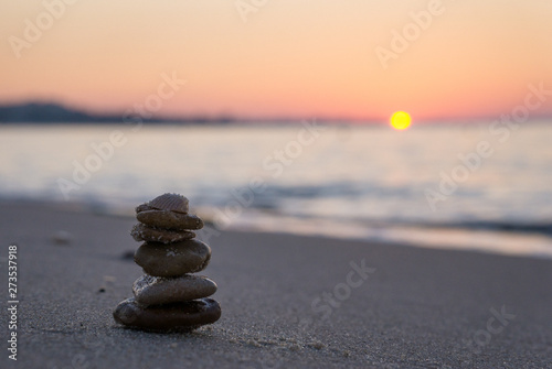 Poster de jardin Zen pierres a sable Zen stone sculpture - pebble - and calm sea at sunrise in Tunisia. Vacation.