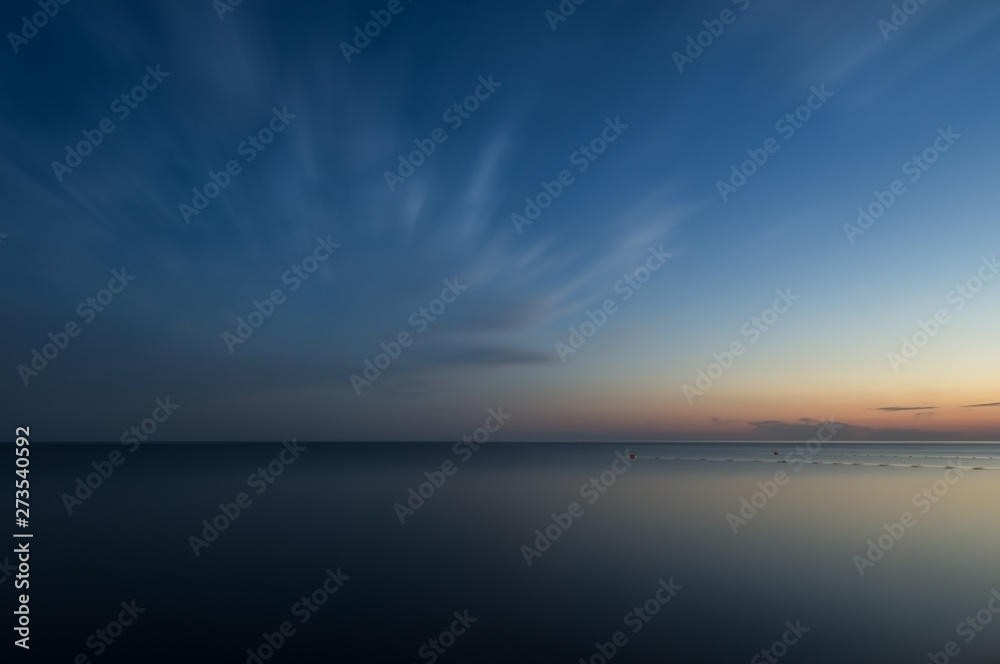 Fototapety, obrazy: Long exposure. Evening sea under the clouds. The surface of the water turned into a flat surface. Blue sky on water reflections of the sunset. The blurred fence in the water.