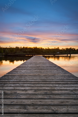 Wooden pier stretching into the lake on a background of dawn. Vertical frame