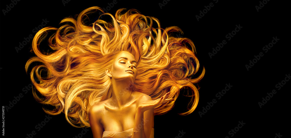 Fototapeta Golden beauty woman. Sexy model girl with golden makeup and long hair pointing hand over black. Metallic gold glowing skin and fluttering hair - obraz na płótnie