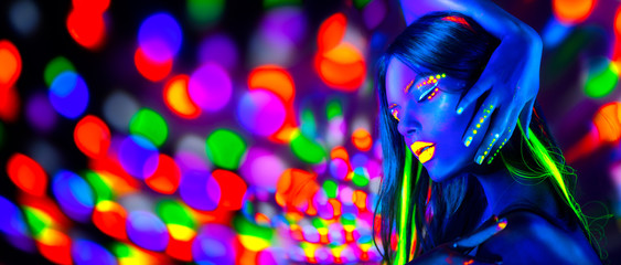 Sexy girl dancing in neon lights. Fashion model woman with fluorescent makeup posing in UV on bright background