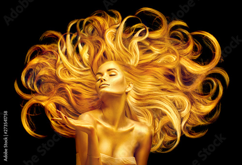 Fototapeta Golden beauty woman. Sexy model girl with golden makeup and long hair pointing hand over black. Metallic gold glowing skin and fluttering hair obraz na płótnie
