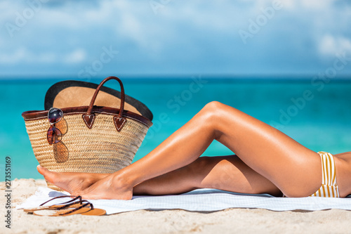Suntan beach vacation woman legs lying on sand towel relaxing on summer holidays. Body care sexy toned leg for cellulite or hair removal laser treatment concept. - 273551169