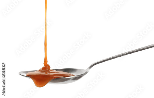 Carta da parati  Tasty caramel sauce pouring into spoon isolated on white