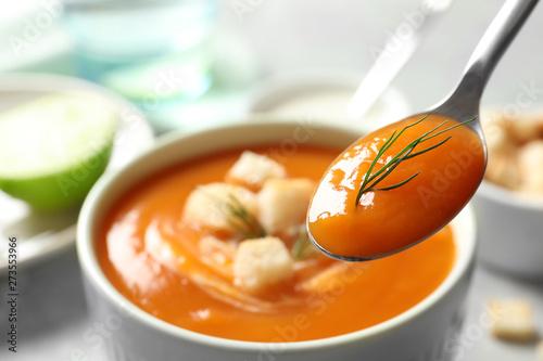 Fotografie, Obraz  Spoon with tasty sweet potato soup over table, closeup
