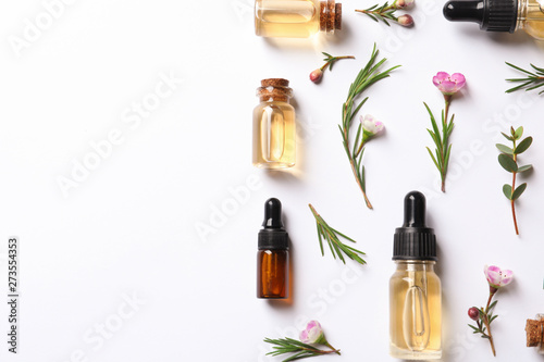 Fototapeta Flat lay composition with bottles of natural tea tree oil on white background obraz
