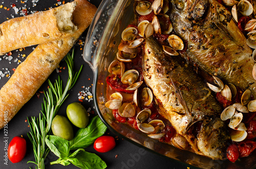 Fényképezés  Grilled dorada fish with clams in dish, italian olive bread and rosemary on dark background