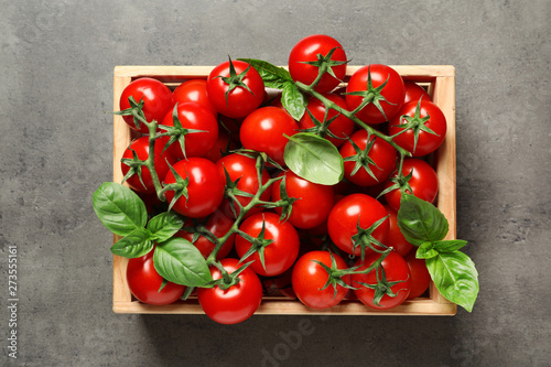Fotografia, Obraz Crate with fresh cherry tomatoes on stone background, top view