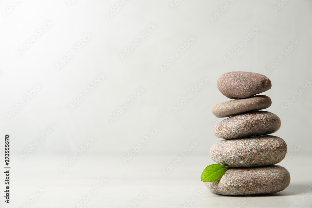 Fototapeta Stack of spa stones with leaf on light background. Space for text