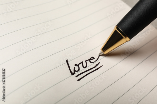 Writing word LOVE in journal, closeup view