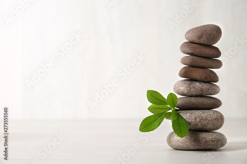 Photo  Stack of spa stones with branch on light background