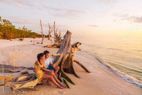 Beach sunset couple relaxing on summer honeymoon vacation travel watching sunset at Florida beach, Gulf of Mexico, USA travel. Man and woman at Lover's key. - 273555720