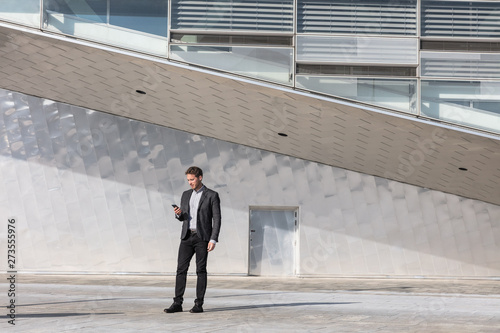 Fototapeta Businessman using mobile phone app texting outside of office in urban modern city building background. Young caucasian man holding smartphone for business work. obraz