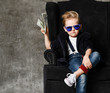 canvas print picture - Happy and shoutting rich kid boy millionaire sits with a bundle of money dollars cash in big luxury armchair while bills falling