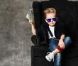 Leinwandbild Motiv Happy and shoutting rich kid boy millionaire sits with a bundle of money dollars cash in big luxury armchair while bills falling