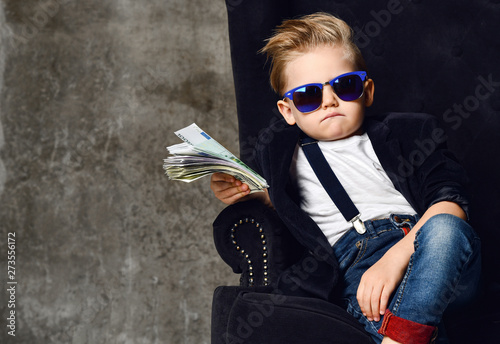 Fototapeta Happy and shoutting rich kid boy millionaire sits with a bundle of money dollars cash in big luxury armchair while bills falling obraz