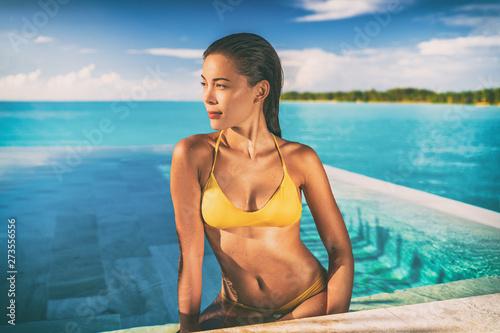Sexy Asian bikini model woman sun tanning in infinity pool at luxury hotel in Bora bora , Tahiti, French Polynesia Wallpaper Mural
