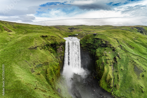 Iceland waterfall Skogafoss in Icelandic nature landscape. Famous tourist attractions and landmarks destination in Icelandic nature landscape on South Iceland. Aerial drone view of top waterfall. - 273563359