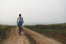 White Caucasian Young Woman In Casual Clothing Riding On Bicycle In Countryside Road Evening At Sunset, View From Back In Full Body Size, Lifestyles Stock Photo Image