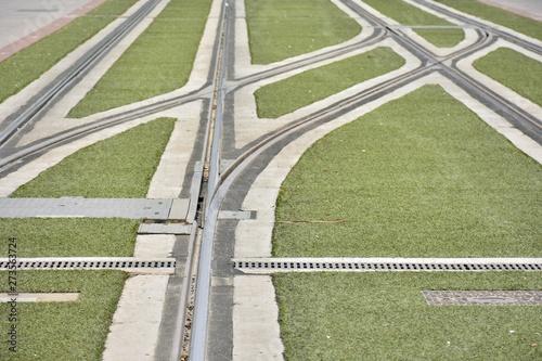 Cruce de vías de un tranvía urbano con césped artificial - 273563724