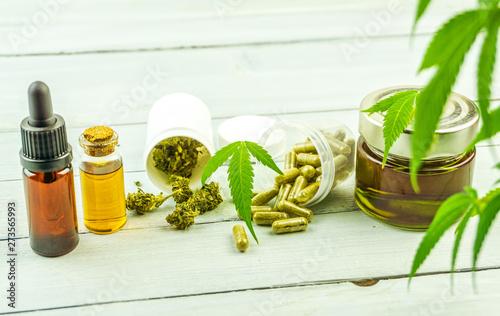 Photo CBD cannabidiol oil glass bottles, pills flower buds and Cannabis leafs on brigh