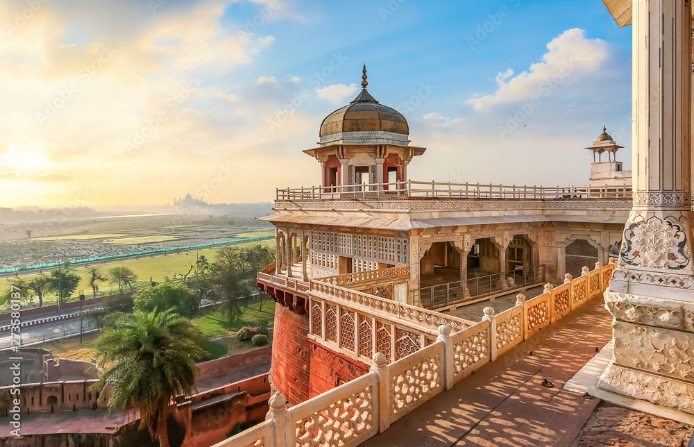 Fototapety, obrazy: Agra Fort - Medieval Indian fort made of red sandstone and marble with view of dome at sunrise. View of Taj Mahal at a distance as seen from Agra Fort.