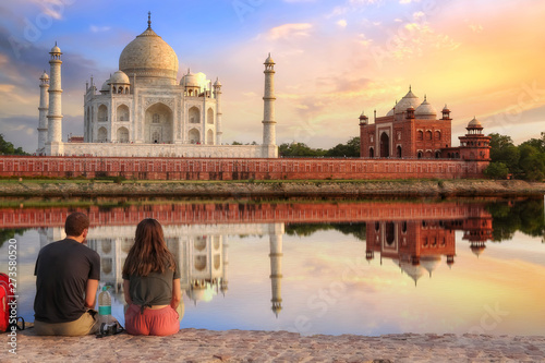 Taj Mahal Agra at sunset with moody sky and water reflection enjoyed by tourist Fotobehang