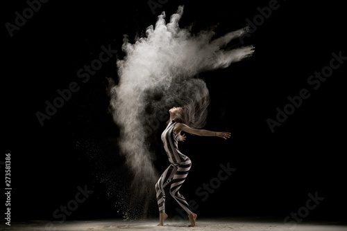 Photographie Graceful girl dancing in dust cloud in the dark