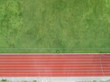 Aerial top view on Half of soccer field, football field with red running track. race track in a stadium.