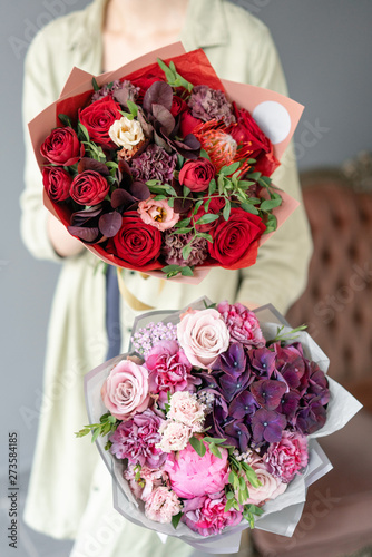Two Small Beautiful bouquets of mixed flowers in woman hand. Floral shop concept. Flowers delivery © malkovkosta