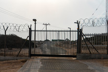 Automatic Metal Gate. Barbed Wire Fence Block The Way. Gate To A Closed Area.