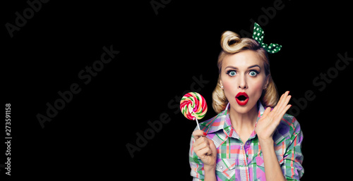 Fototapeta  Photo of beautiful very surprised woman with lollipop, in pinup style, over blac